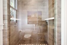 a bold shower space with a mosaic tile floor and wood look tiles on the walls for a warm feel and look here