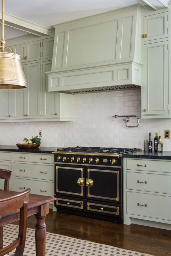 a bright art deco kitchen in pale green, with a white tile backsplash, a vintage cooker and gold touches