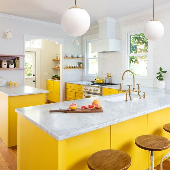 a bright kitchen done with yellow cabinets, white stone countertops and all white everything for a chic and bold look