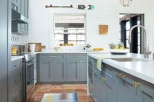 a bright kitchen with grey cabinets, white walls and countertops and touches of gold here and there