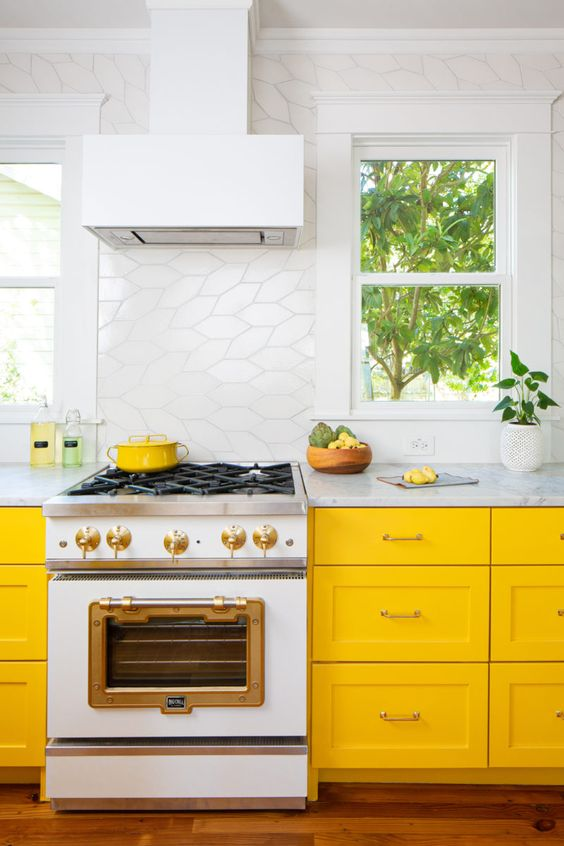 a bright kitchen with sunny yellow cabinets, a catchy white tile backsplash and all white everything for a fresh feel