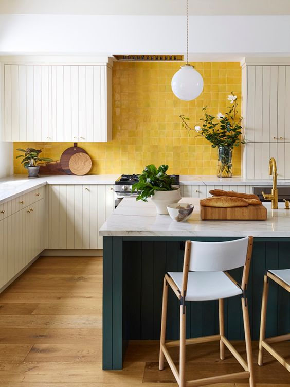 a bright kitchen with white plank cabinets, a yellow tile backsplash and teal kitchen island with stone countertops
