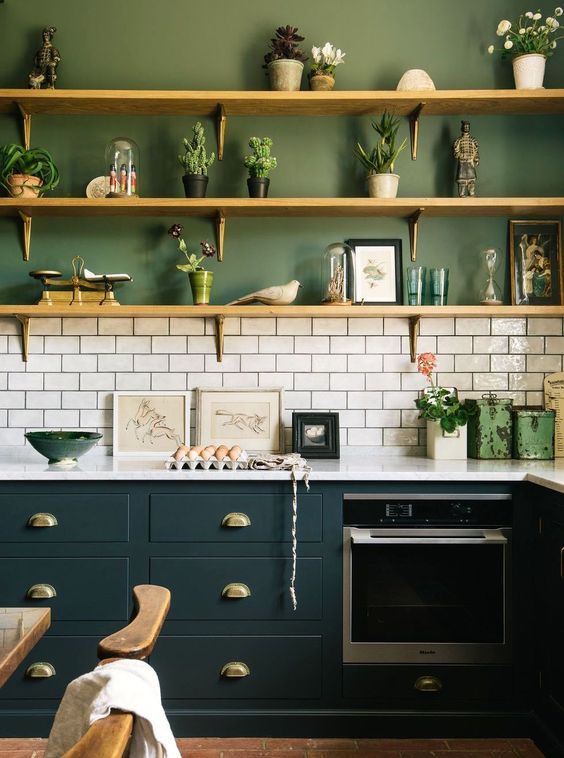 a catchy modern kitchen with green walls, whihte subway tiles and teal cabinets diluted with wooden shelves