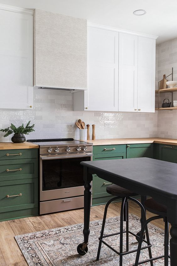a chic and bold kitchen with white and green cabinets, metallic touches, wooden countertops and a dark grey kitchen island
