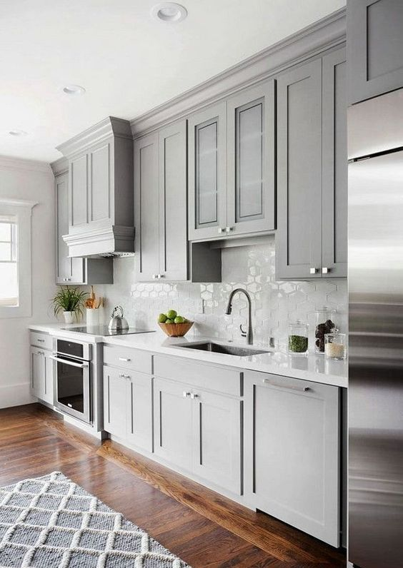 a chic contemporary dove grey kitchen with a white tile backsplash and countertops plus a rich stained floor