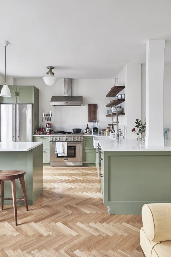 a chic contemporary kitchen in light green and white, with dark wooden touches and white countertops is very welcoming