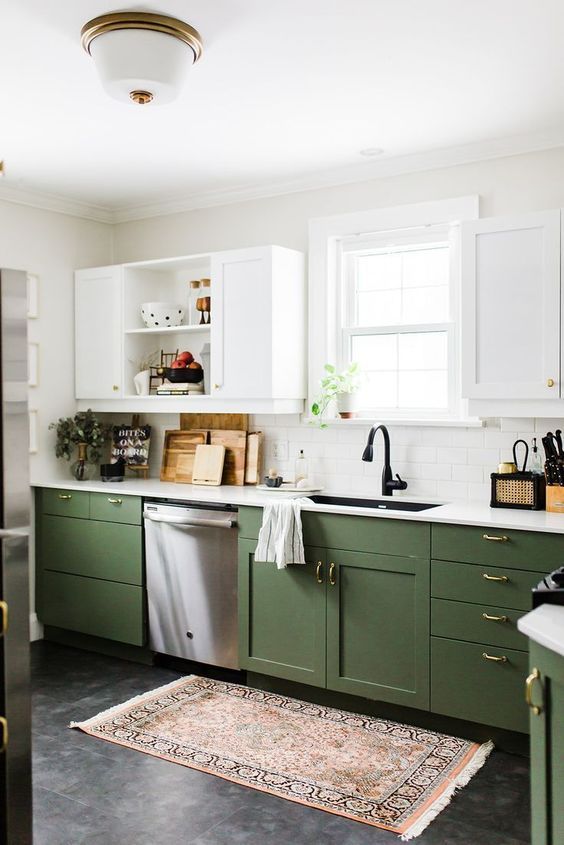 a chic contemporary kitchen with green and white cabinets, gold handles and white countertops plus a boho rug