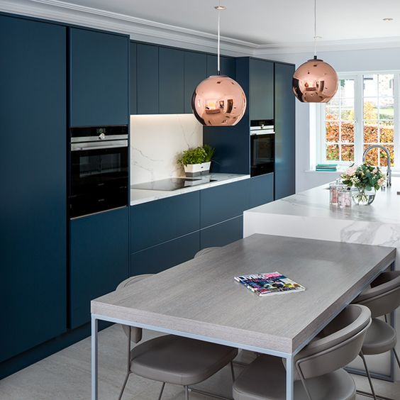 a chic contemporary navy kitchen with a white kitchen island and matching countertops plus a grey table for breakfasts
