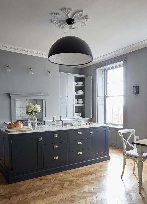 a chic dove grey kitchen with a midnight blue kitchen island and touches of brass that make it more refined and gorgeous