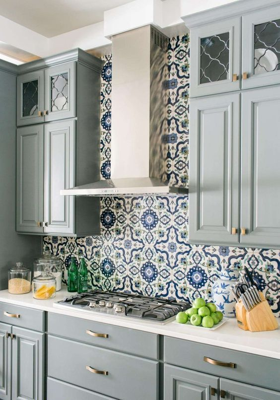 a chic grey kitchen with a bright blue and white mosaic tile backsplash and white countertops is bright and refined