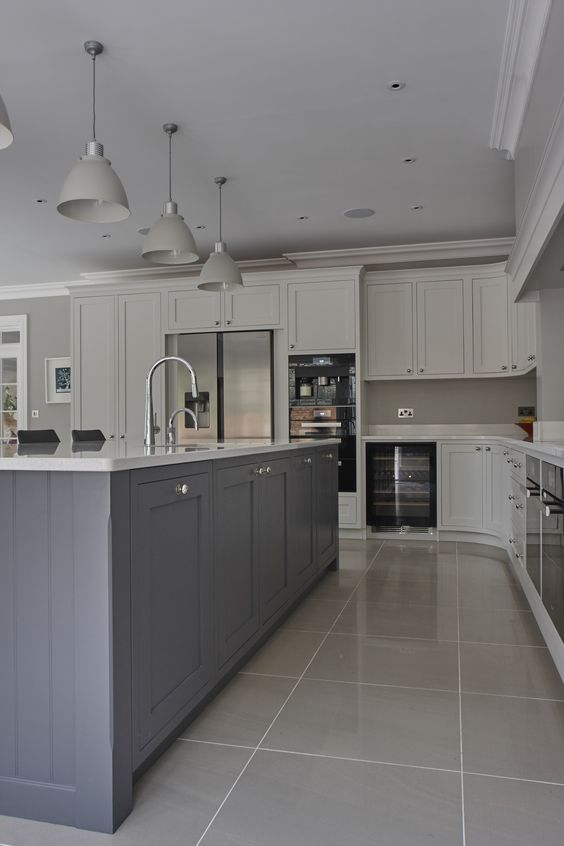 a chic kitchen with dove grey cabinets, a pale blue kitchen island, grey lamps and white stone countertops