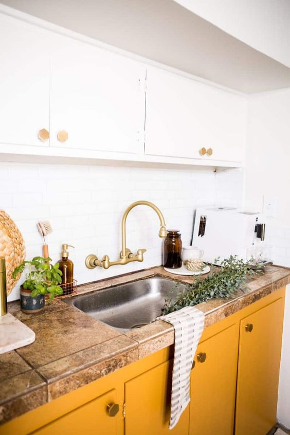 a chic kitchen with white upper cabinets and buttercream lower ones plus a stone countertop and brass touches looks cool