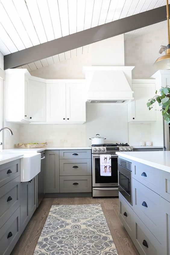 a chic two tone kitchen with white upper cabinets and light grey lower ones, black handles and dark wooden beams