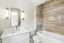 a contemporary bathroom done in white and with wood look tiles over the bathtub to highlight this zone