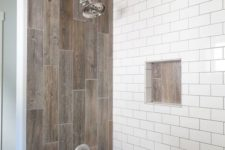 a contemporary bathroom done with white subway tiles and wood look tiles over the tub for a chic and bold look