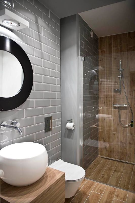 a contemporary bathroom with grey tiles and wood look ones in the shower space and on the floor for a warm feel