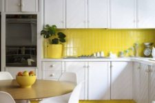 a contemporary kitchen done in lemon yellow and white, with textural cabinets and a wooden floor looks bold