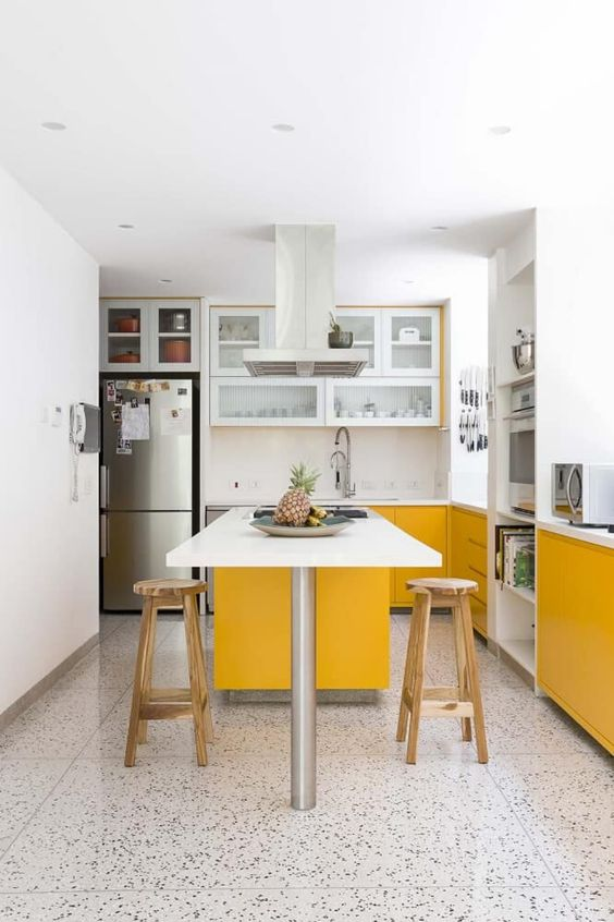 a contemporary kitchen done with sunny yellow and white cabinets, with white countertops and a mosaic floor looks cool