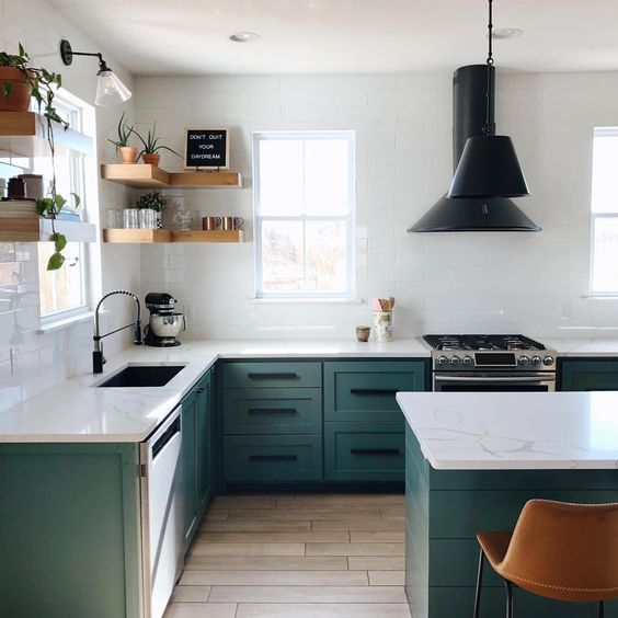 a contemporary kitchen with green cabinets, white tile walls, white stone countertops and black fixtures and lamps