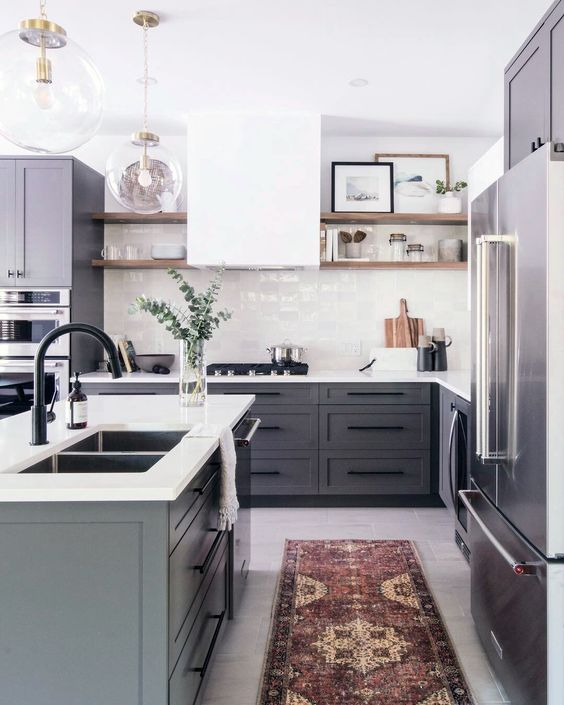 a contemporary kitchen with grey cabinets, a white hood and tile backsplash and white countertops plus a boho rug