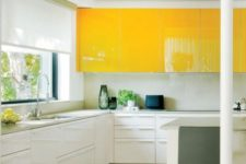 a contemporary kitchen with upper bright yellow cabinets, white ones and a white backsplash looks ultra bold