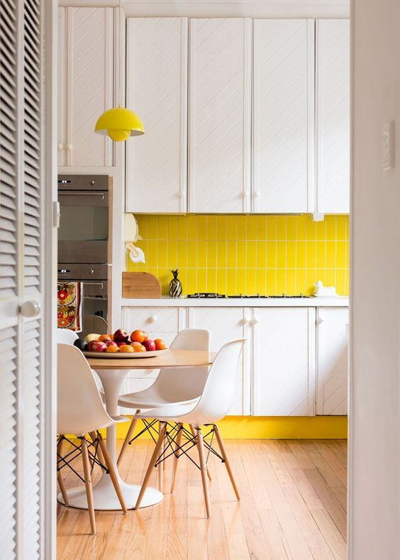 a contemporary kitchen with white cabinets, a bright yellow tile backsplash and a lamp, white chairs and neutrals