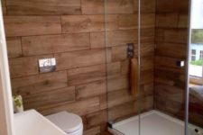 a contemporary rustic bathroom all clad with wood look tiles – the walls and the floor for a warm feel