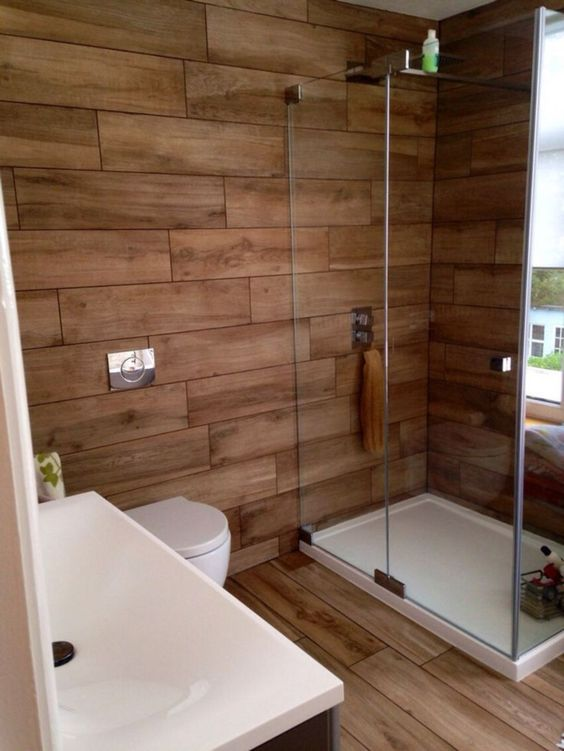 a contemporary rustic bathroom all clad with wood look tiles - the walls and the floor for a warm feel