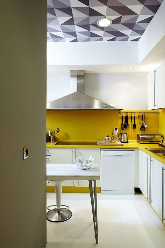 a contemporary white kitchen made bold with a yellow backsplash and countertops plus staineless stele appliances