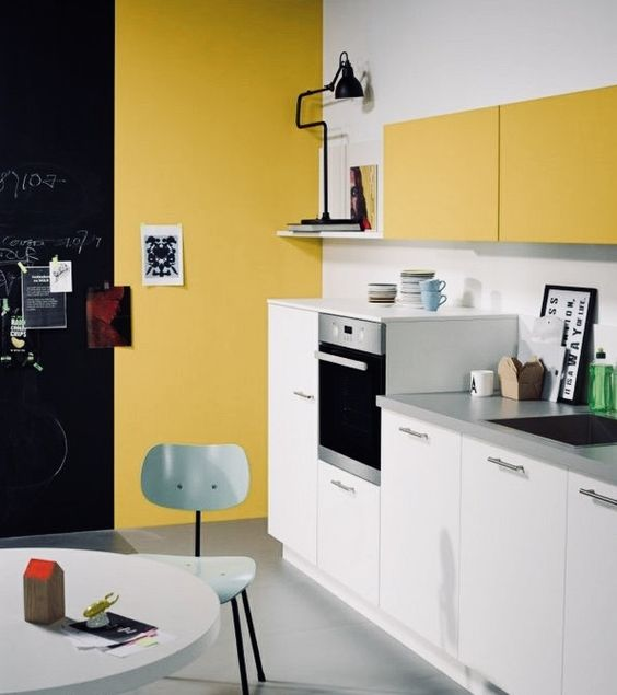 a contemproary kitchen done in mustard and white, with touches of black for some drama