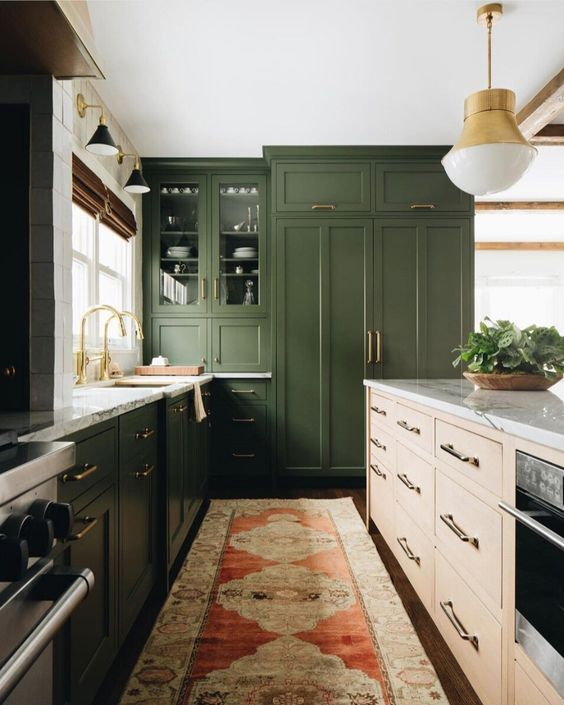 a dark green kitchen, a light colored wood kitchen island, white stone countertops and gold touches for a mid-century modern feel