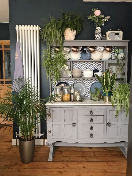 a dining room with a wooden buffet and lots of potted plants all over to refresh the space