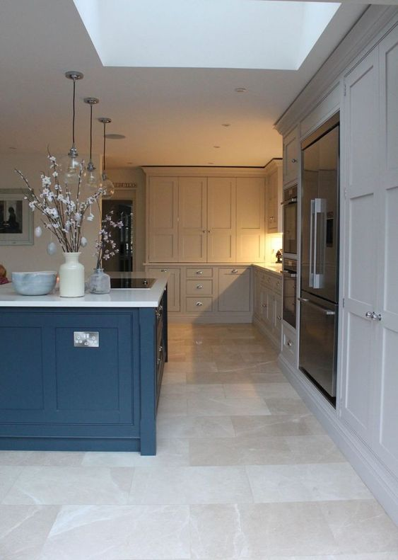 a dove grey kitchen with a bold blue kitchen island, white stone countertops and a neutral tile floor