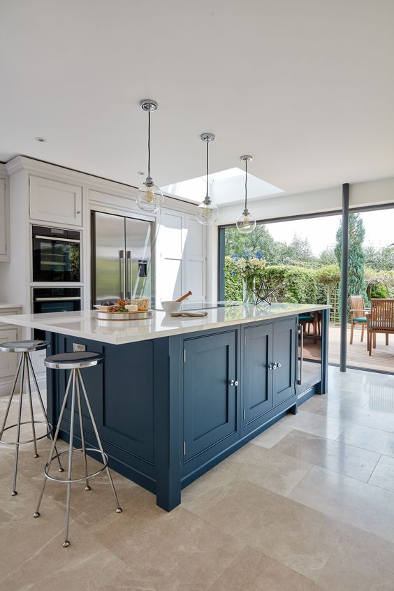 a dove grey kitchen with a large navy kitchen island and white stone countertops plus vintage stools and pendant lamps