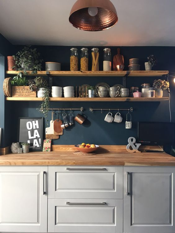 a dove grey kitchen with a navy wall, wooden shelves and butcherblock countertops plus touches of copper and greenery