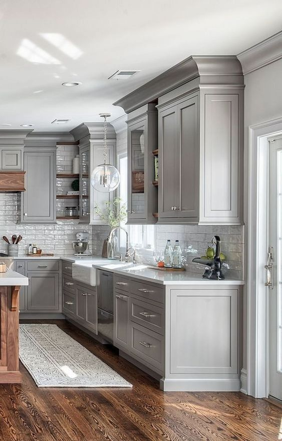 a farmhouse kitchen in dove grey with a white tile backsplash, a bubble lamp and rich stained wood for a warm touch