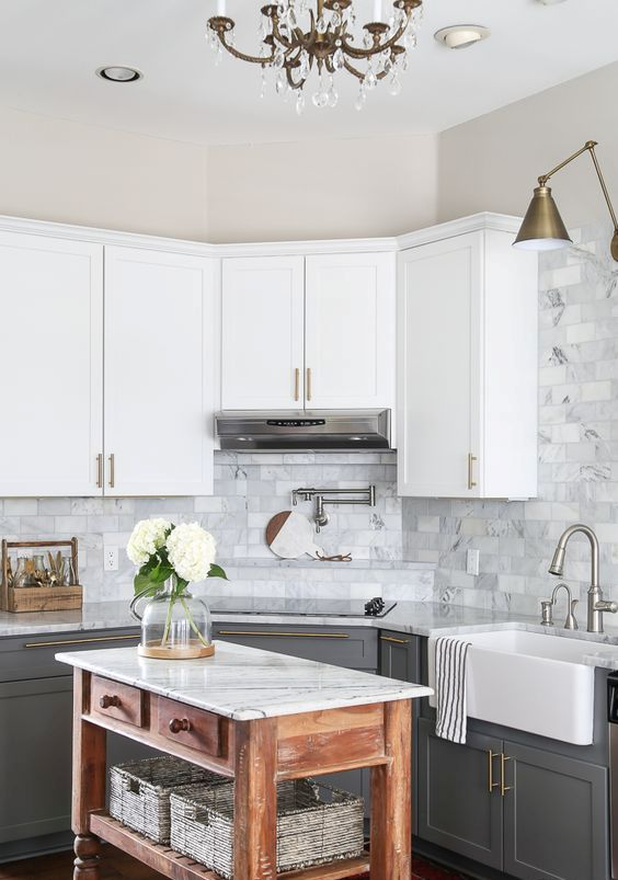 a farmhouse kitchen with upper white cabinets, graphite grey ones, a marble tile backsplash and a stained kitchen island