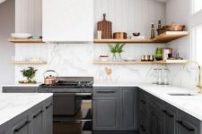 a gorgeous contrasting kitchen with graphite grey cabinets, white countertops and a backsplash, a hood, wooden shelves for a softer look