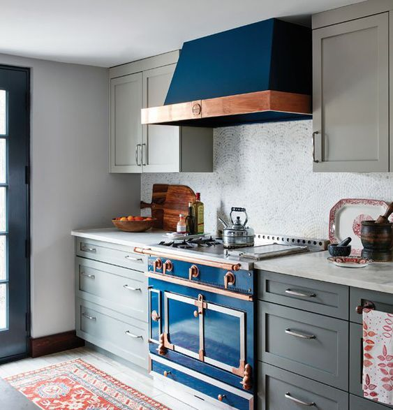 a grey art deco kitchen with a bright blue cooker and copper touches plus a mosaic tile backsplash looks wow