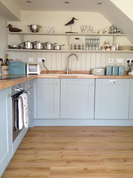 a light blue kitchen with a dove grey wall and beadboard backsplash plus wooden countertops to make the look warmer and softer