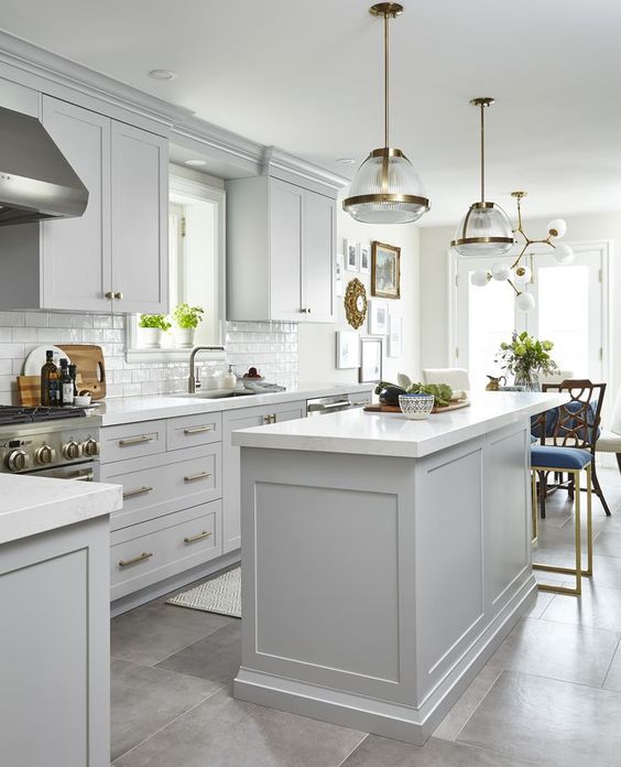a mid century modern kitchen with dove grey cabinets, gold touches and chic lamps and chandeliers for a stylish feel