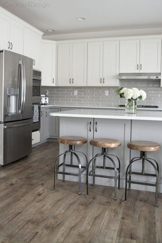 a mid century modern kitchen with dove grey lower cabinets, white upper ones, a grey tile backsplash and a grey kitchen island