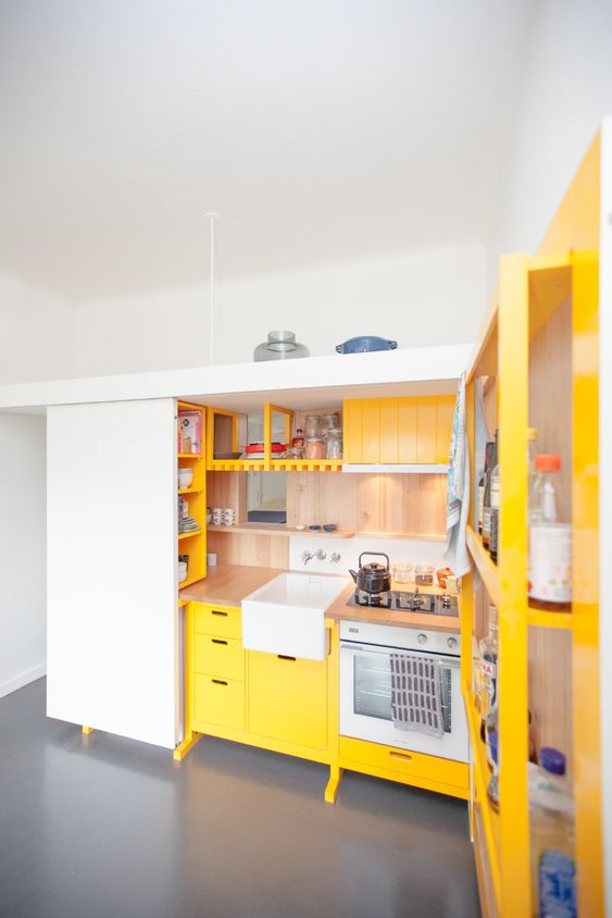 a mini contemporary kitchen done in sunny yellow and with natural wood touches plus built-ins is bold