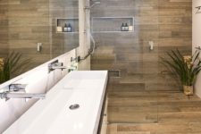 a minimalist bathroom all clad with wood look tiles and refreshed with a white vanity and a long sink