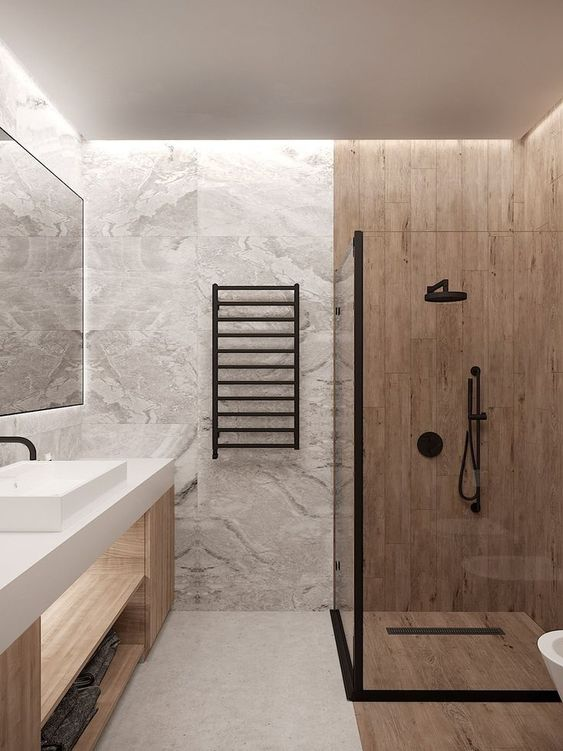 a minimalist bathroom clad with grey marble tiles, a wood vanity and wood look tiles in the shower space
