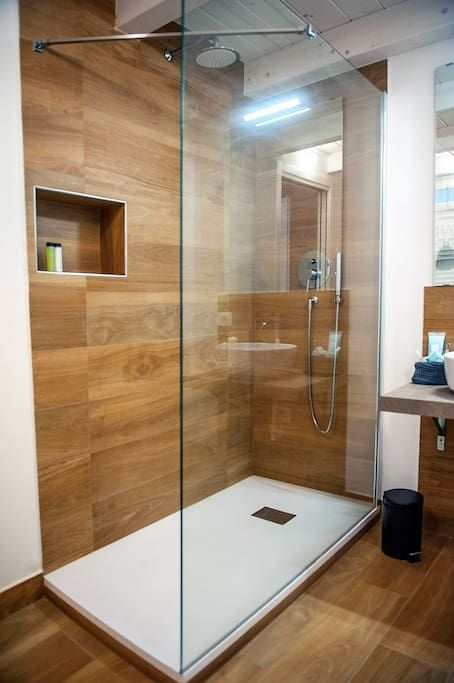 a minimalist bathroom done with warm wood look tiles and some white surfaces to refresh the space