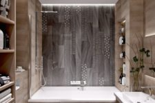 a minimalist bathroom done with wood look tiles and mosaic ones on the floor and bathtub wall for a pattern