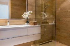 a minimalist bathroom fully clad with wood look tiles on the walls and floor plus a white floating vanity