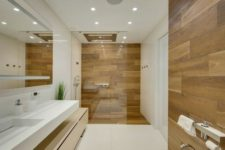 a minimalist bathroom with white large scale tiles and wood look tiles in the shower space and an accent by the toilet