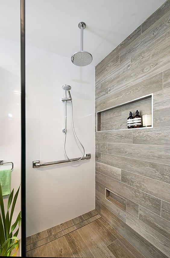 a minimalist bathroom with white surfaces and wood look tiles on the wall and floor for a warm feel in the space